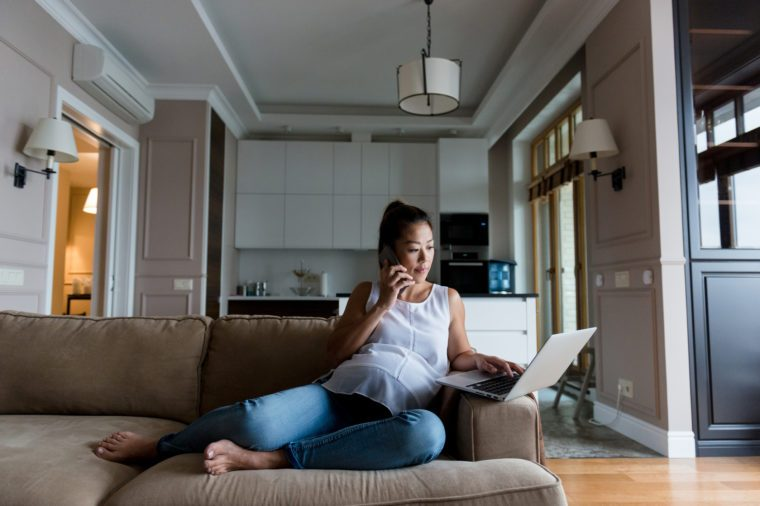 woman working from home on couch with laptop