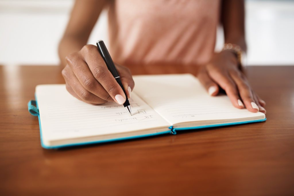close up of woman writing to do list