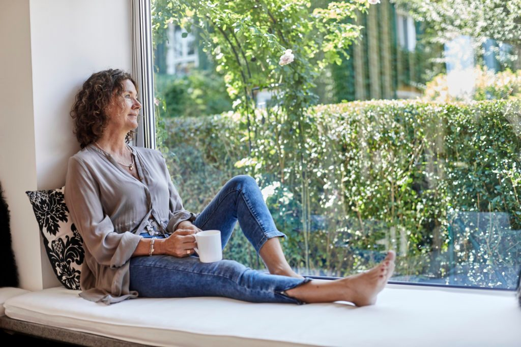 woman sitting on window seat looking out window