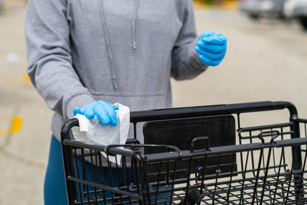 customer wearing gloves and wiping down shopping cart