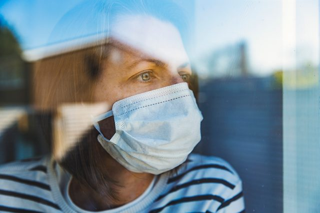 woman at home quarantine isolation looking out of window wearing a surgical mask