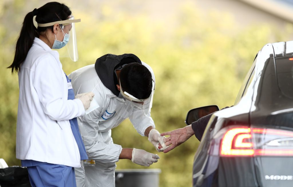 BOLINAS, CALIFORNIA - APRIL 20: A medical professional administers a coronavirus (covid-19) test at a drive thru testing location conducted by staffers from University of California, San Francisco Medical Center (UCSF) in the parking lot of the Bolinas Fire Department April 20, 2020 in Bolinas, California. The town of Bolinas, with a population of 1600, is attempting to test the entire town for COVID-19. The test had two components - the first is a blood test that will look for antibodies, and the second is a mouth and throat swab that can detect active coronavirus infections.