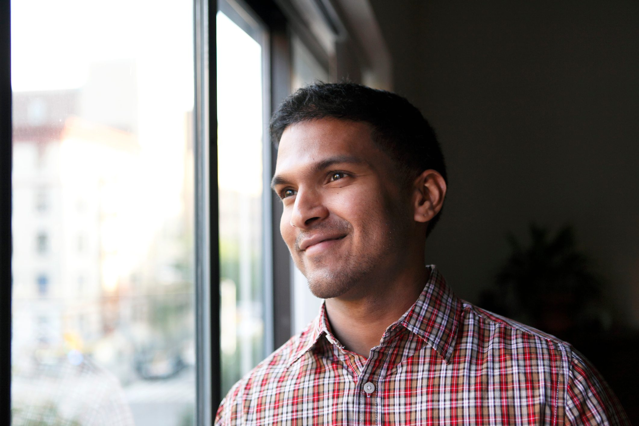 man smiling looking out window