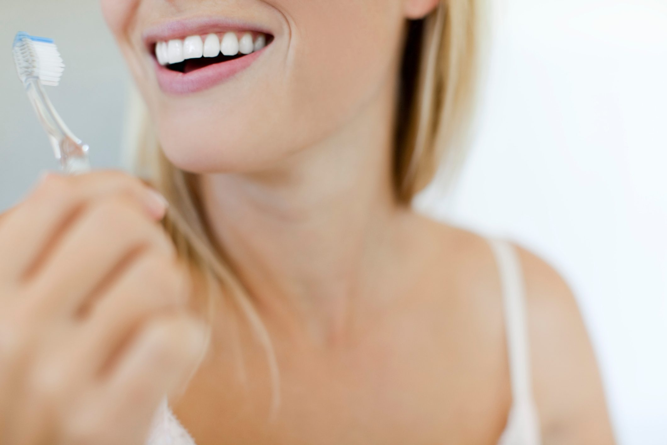 cropped shot of woman brushing teeth
