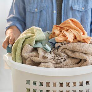 close up of man holding laundry hamper