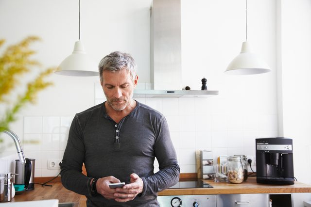 man standing in kitchen looking at smartphone