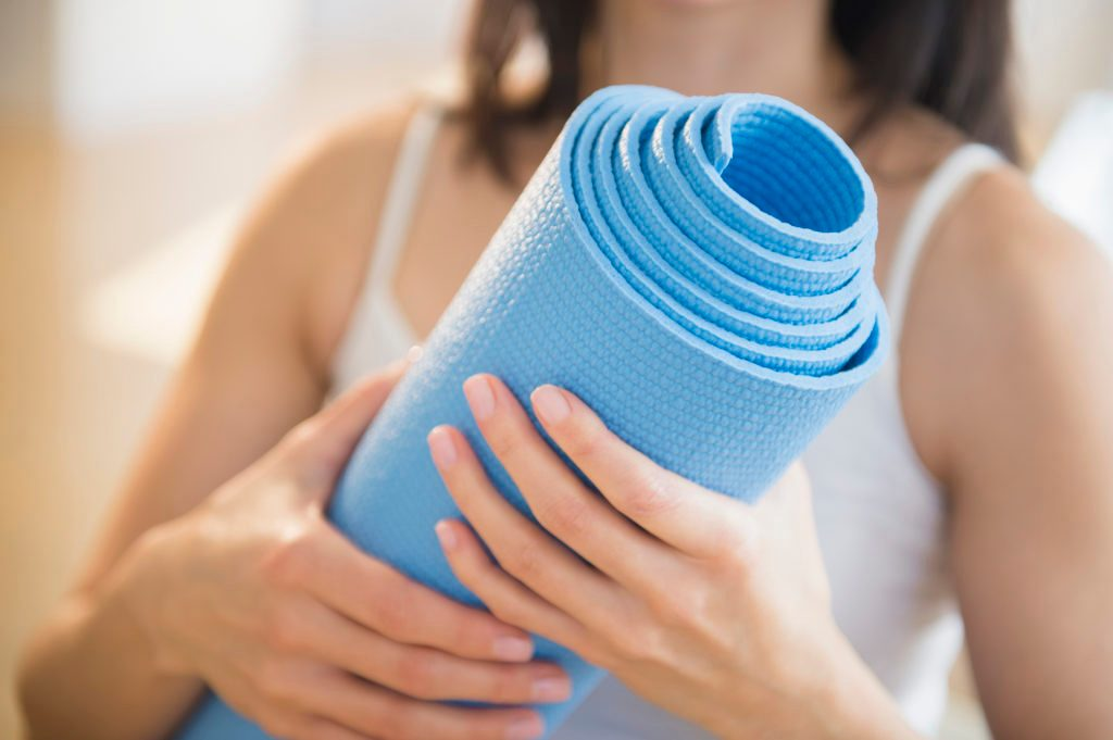 close up of woman holding a blue yoga mat