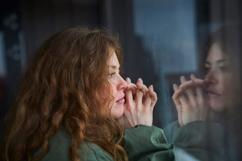 young woman at home looking out window thinking