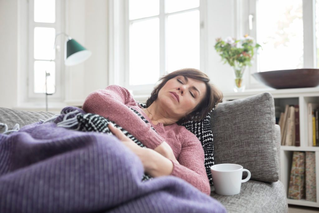 woman laying down on couch with stomach pain
