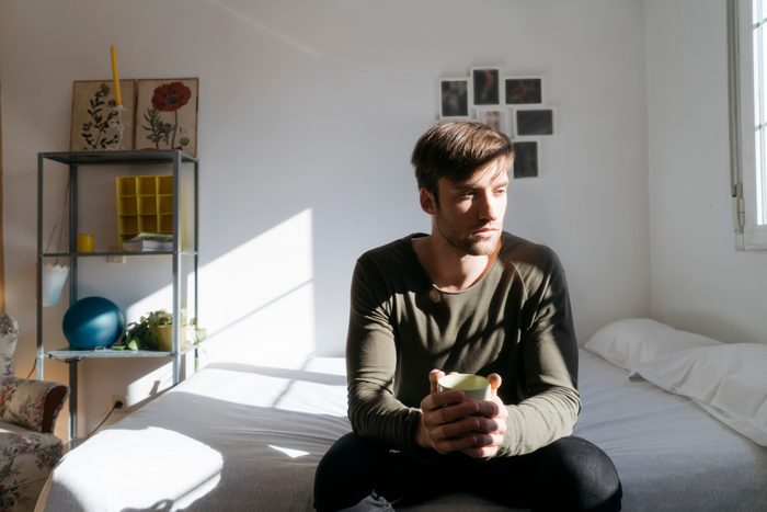 man sitting on edge of bed with coffee
