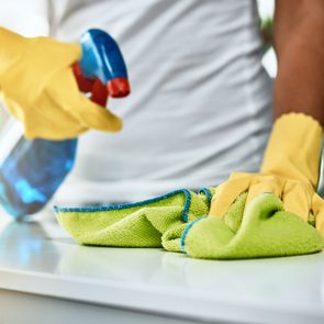 man cleaning and disinfecting home