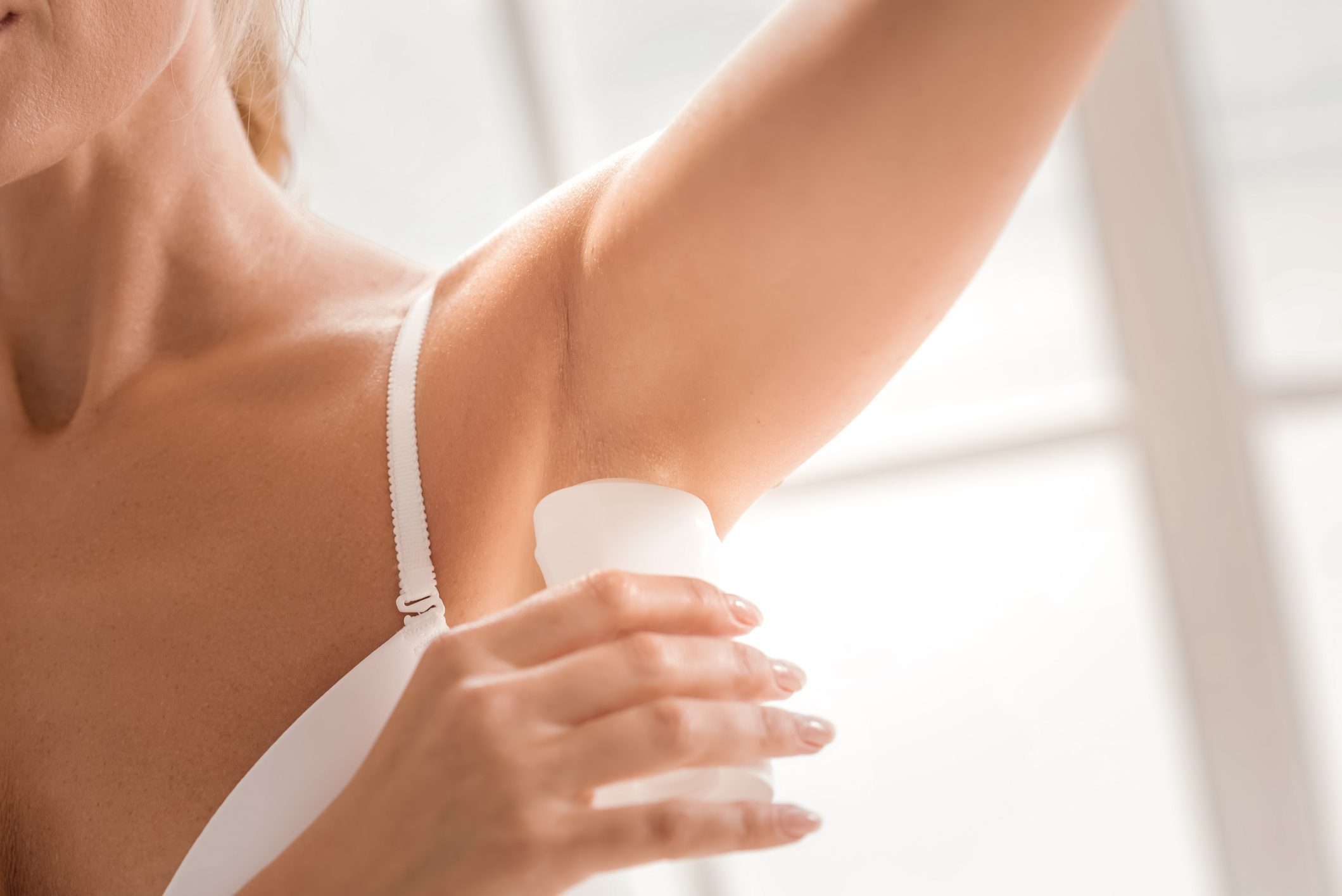 close up of woman applying deoderant