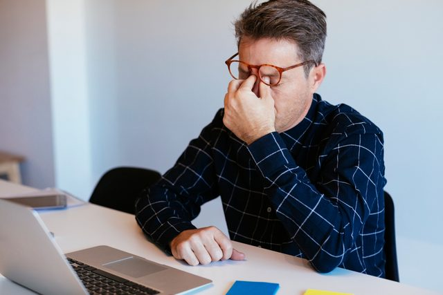 stressed man sitting at desk trying to work