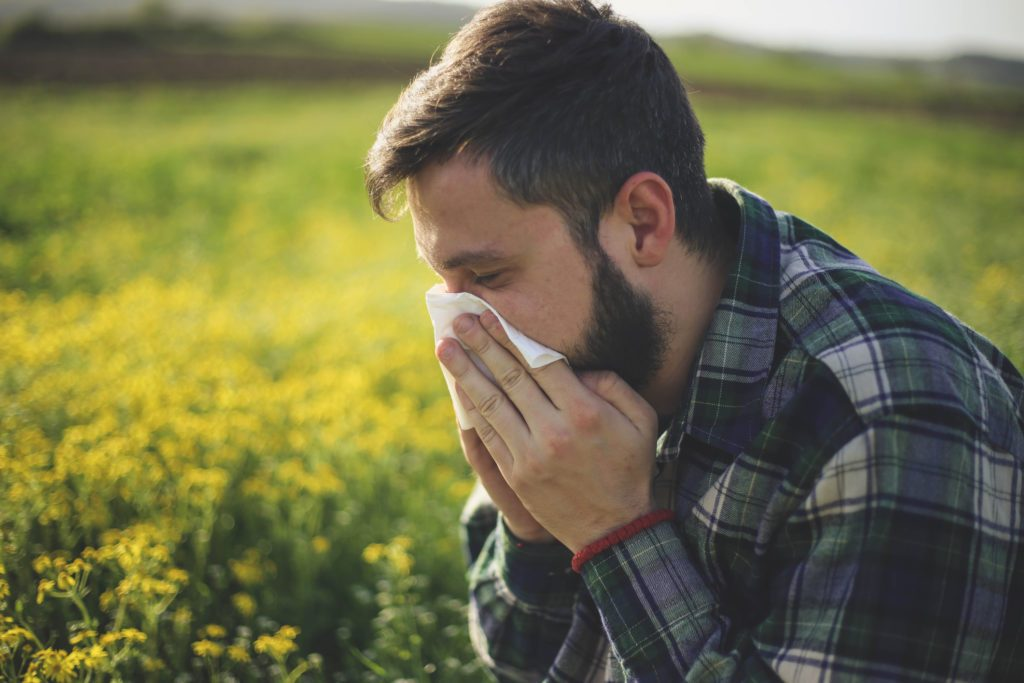 man reacting to spring allergies