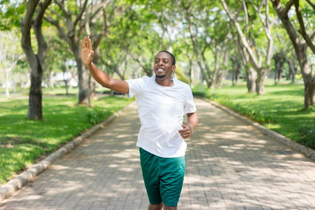 man running outside and waving hi to someone