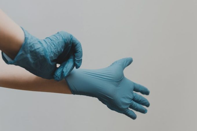 person putting on blue latex medical gloves
