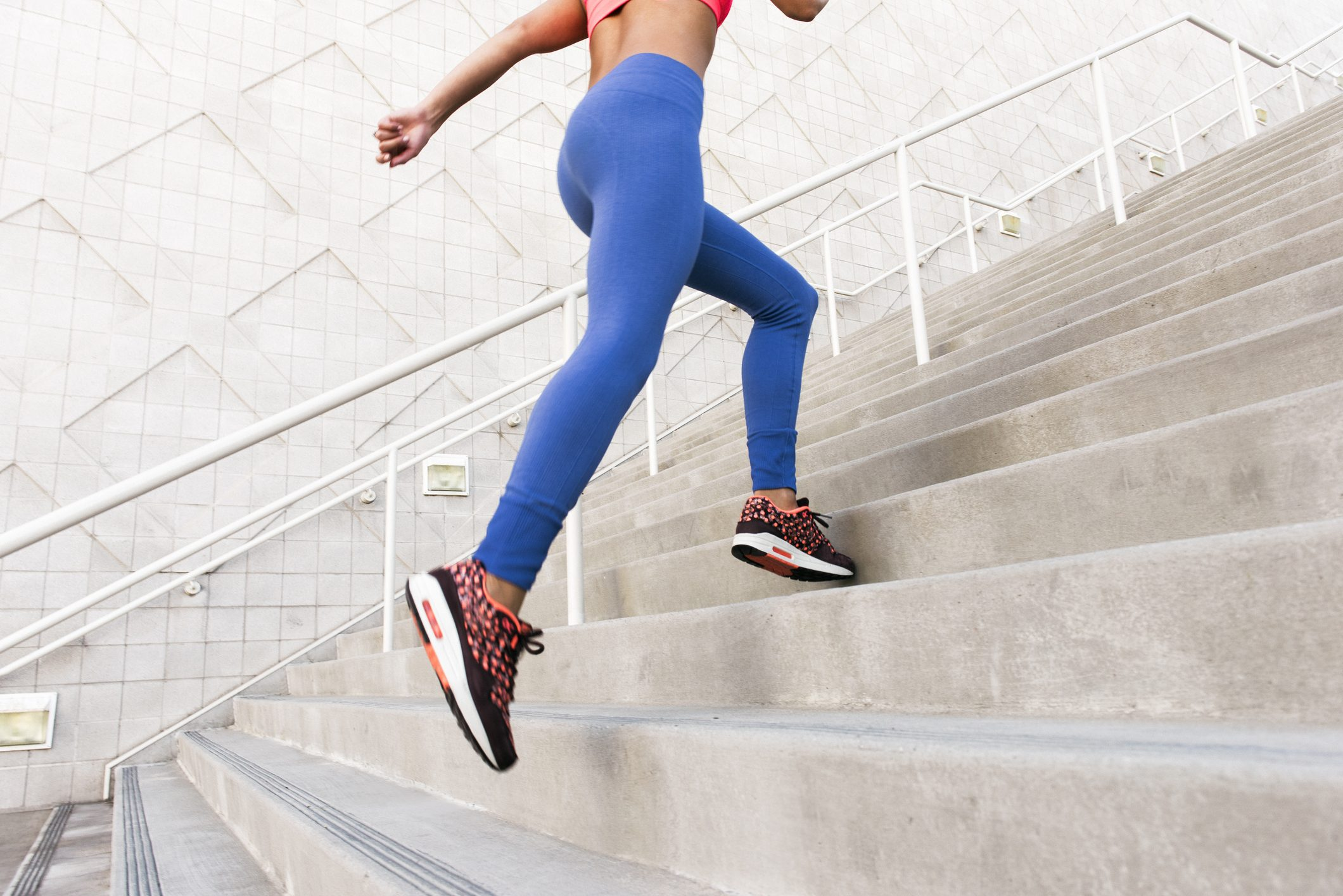 low angle shot of woman exercising on stairs wearing leggings and sneakers