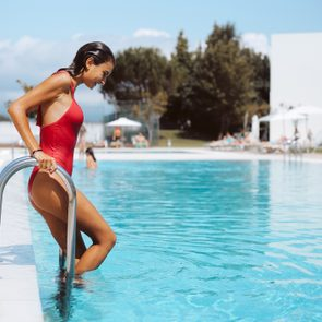 woman getting into swimming pool from ladder