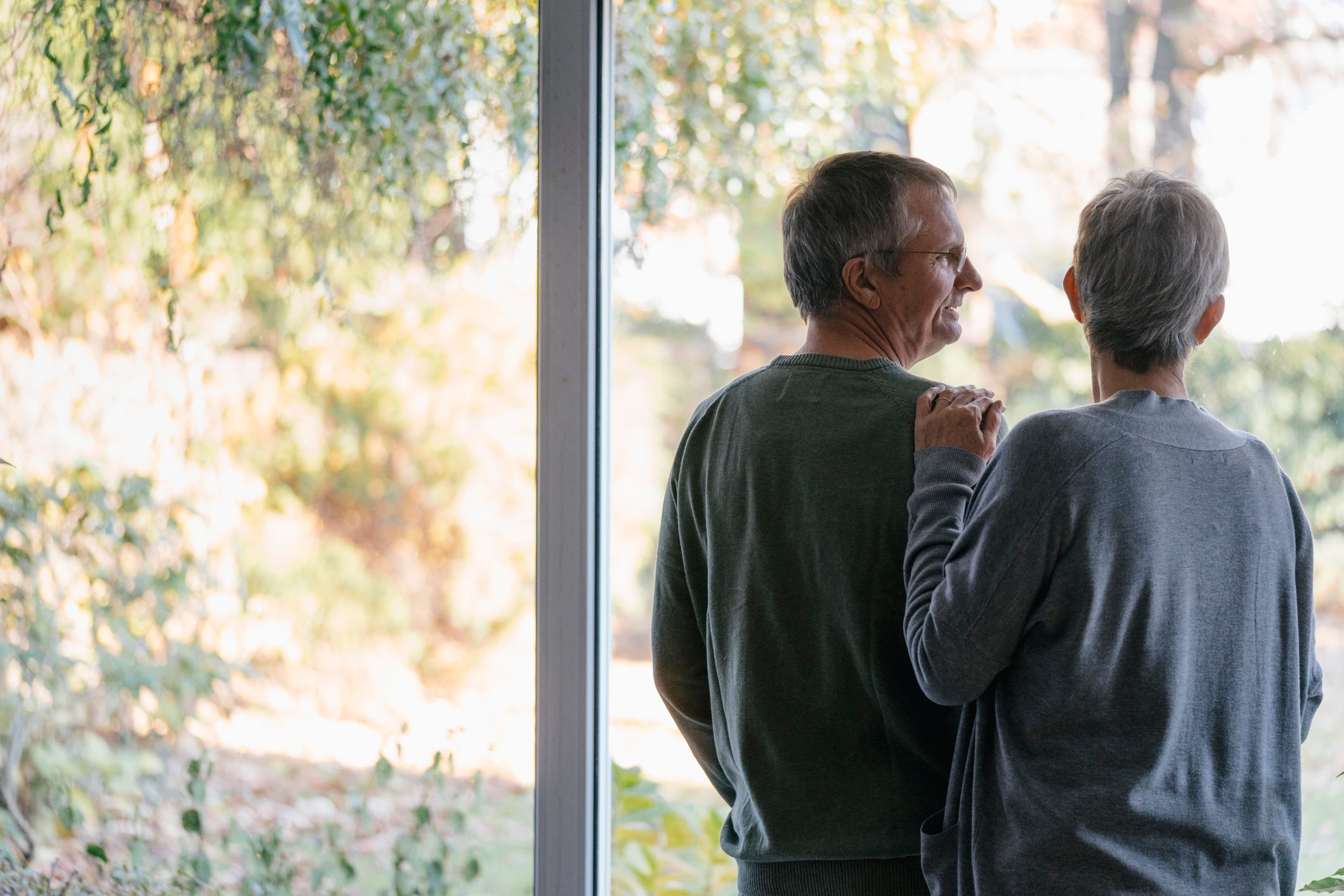 senior couple standing at window in home