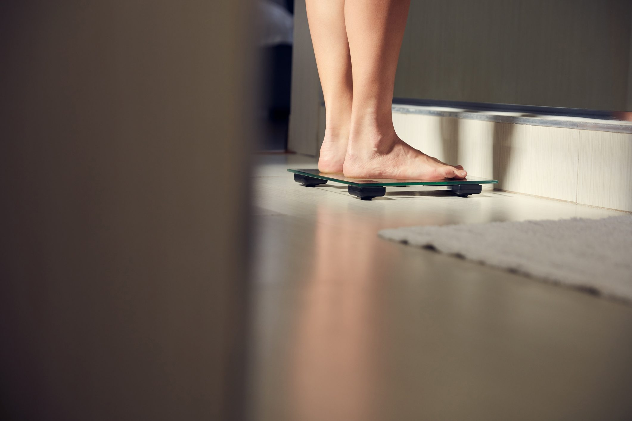 shot of an unrecognizable woman weighing herself on a scale at home in bathroom