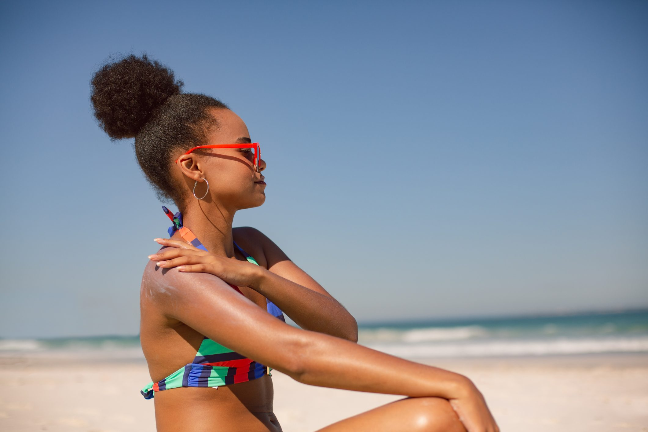 woman sitting on the beach applying sunscreen
