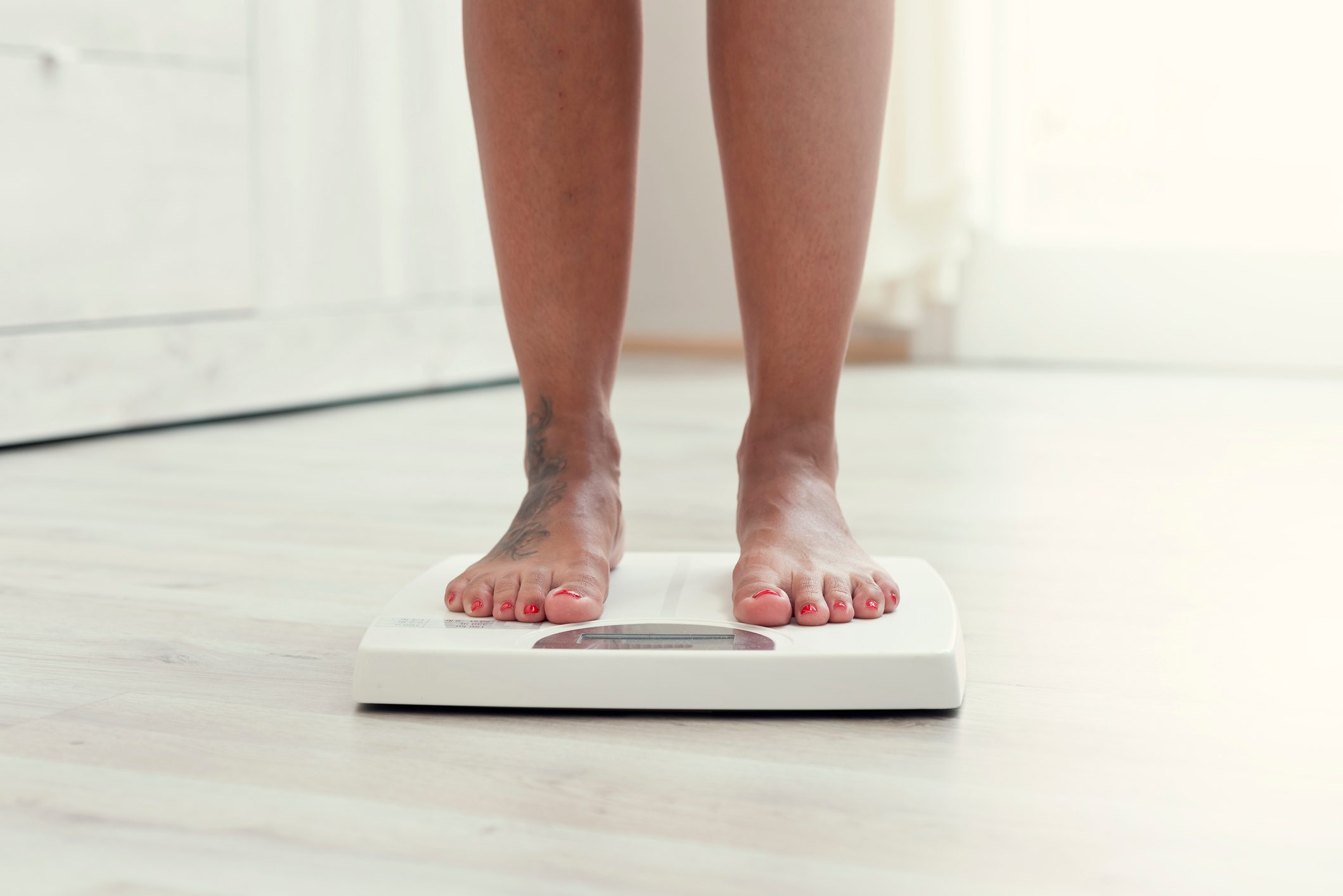 cropped shot of woman's feet on weight scale at home