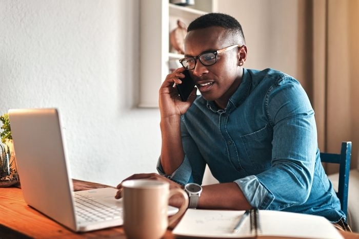 man working at home while talking on the phone