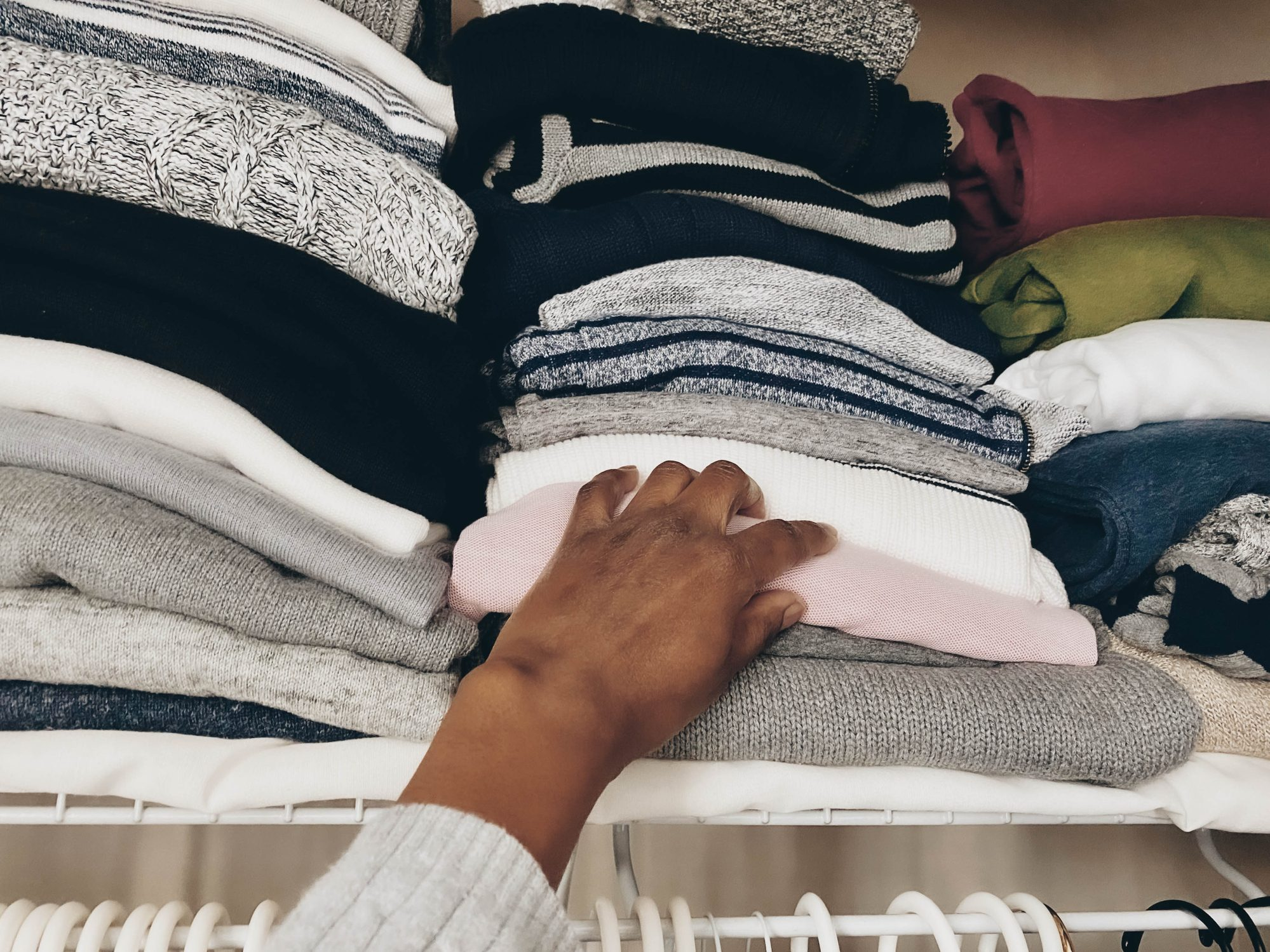 woman grabbing sweater from closet
