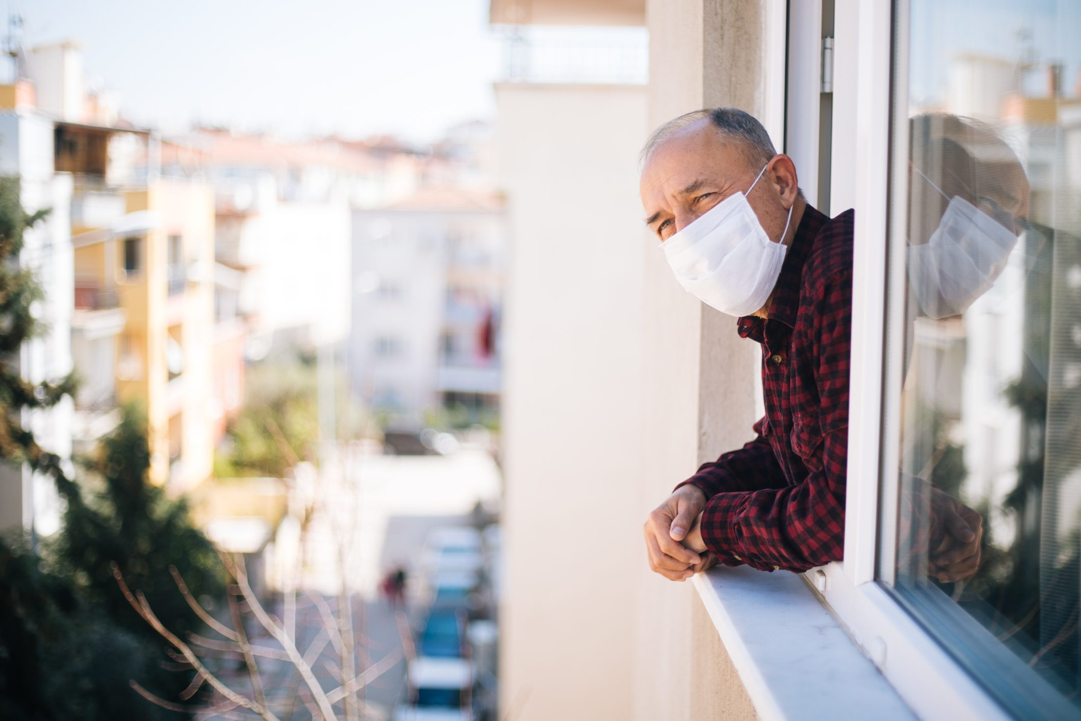man wearing medical mask with head out of window