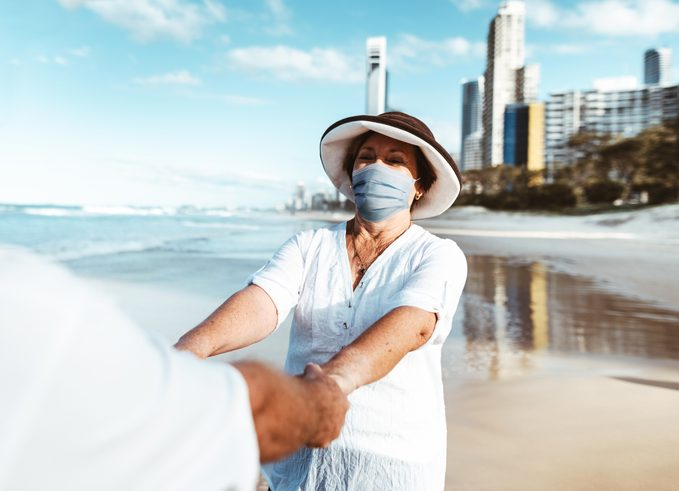 couple at the beach wearing face masks