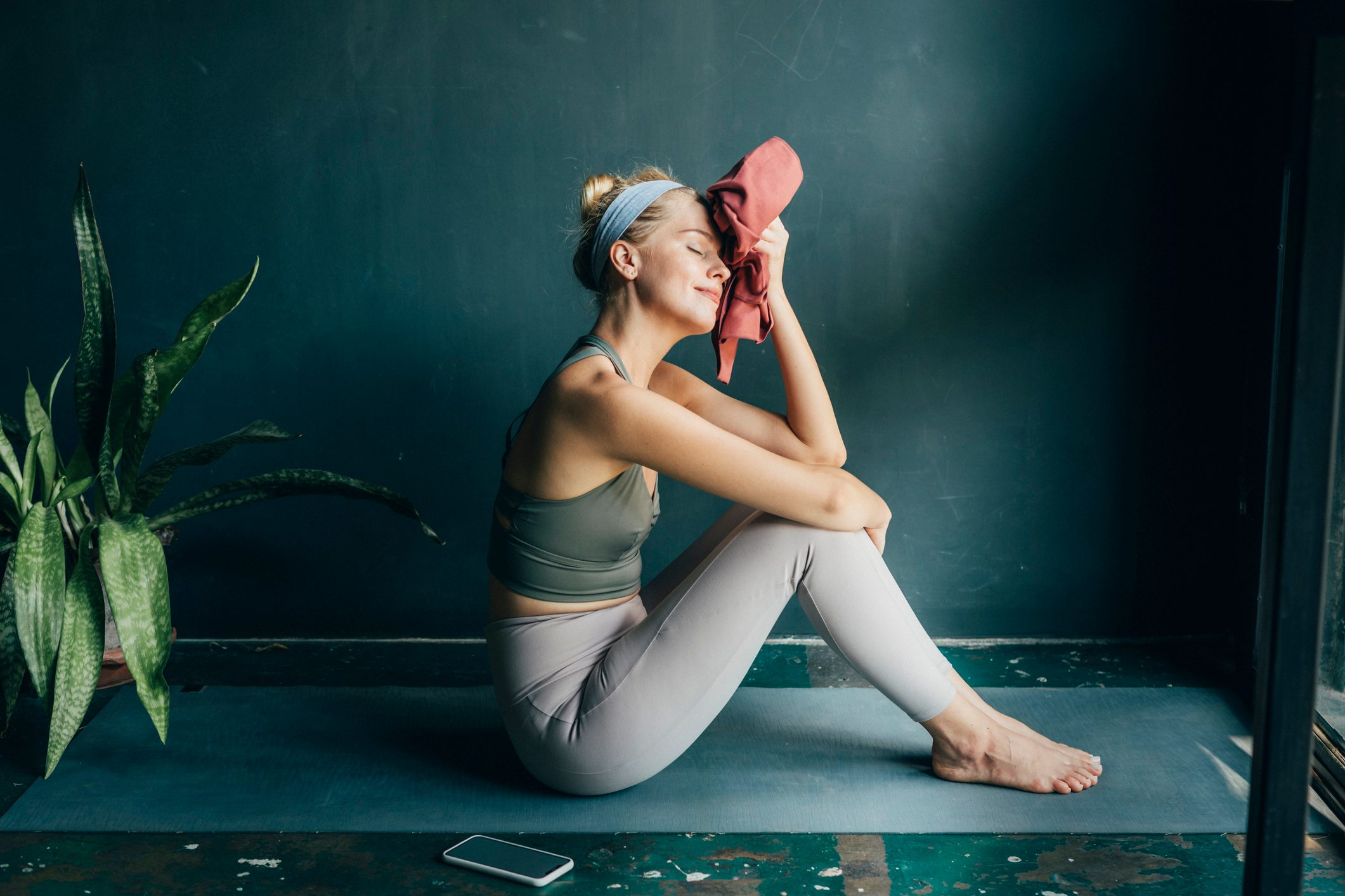 young woman tired from workout sitting on yoga mat