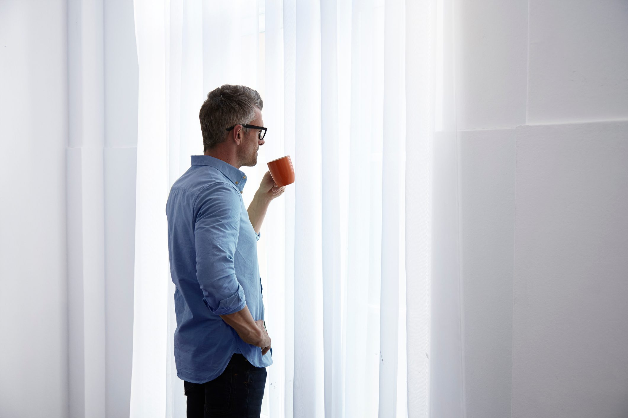 man standing in home looking out window and holding coffee mug