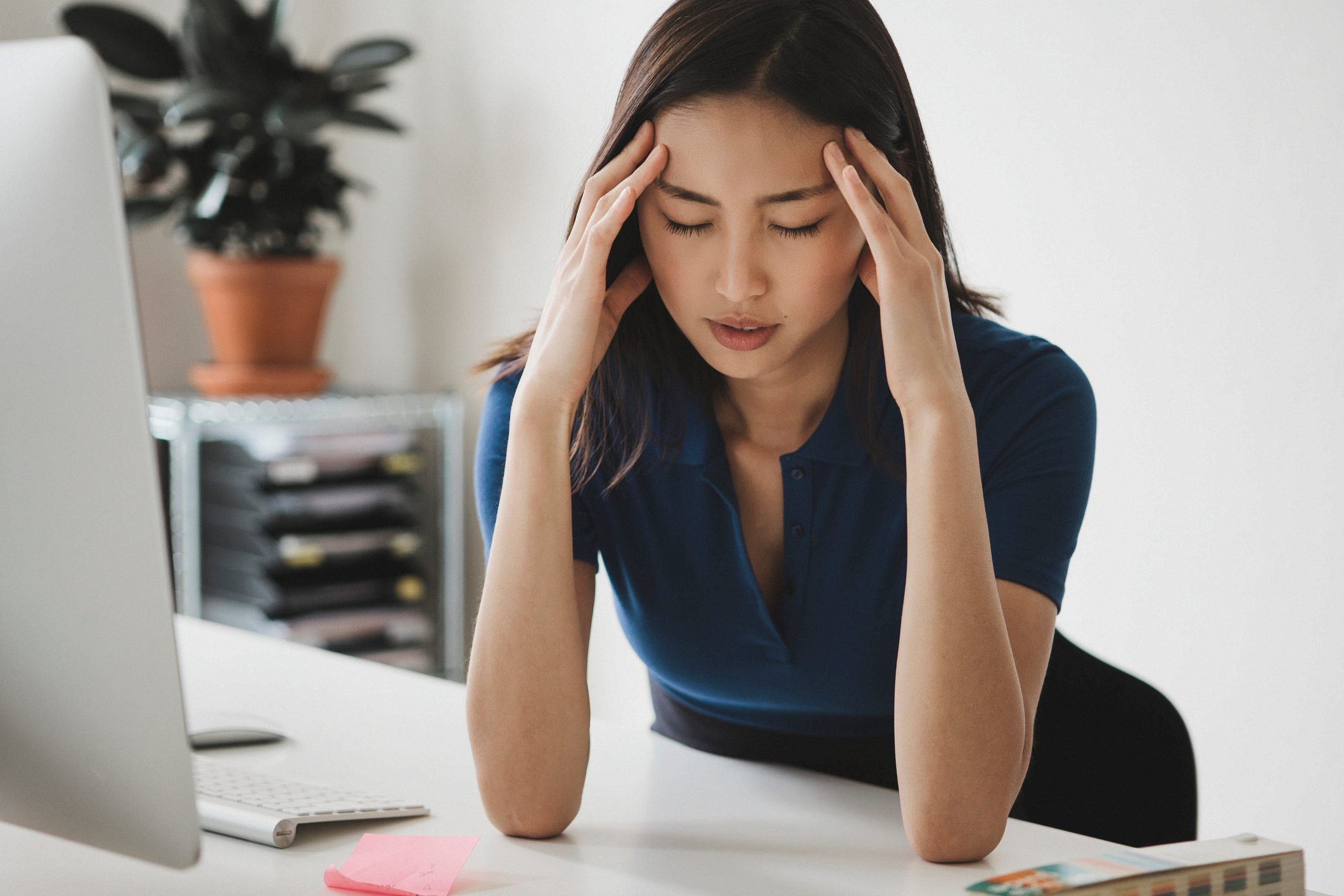 woman suffering from headache while working from home