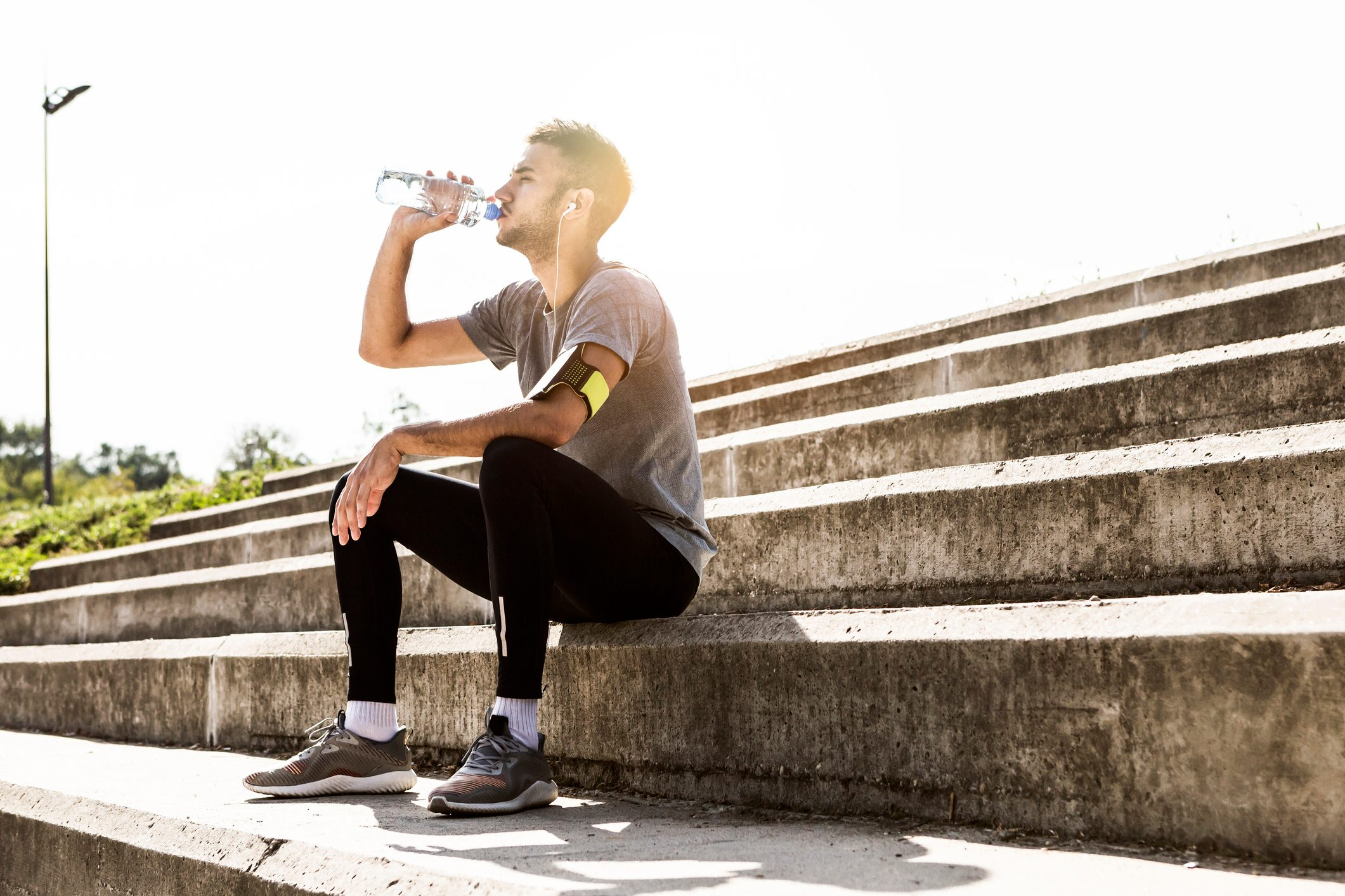 man taking a rest from exercise drinking water