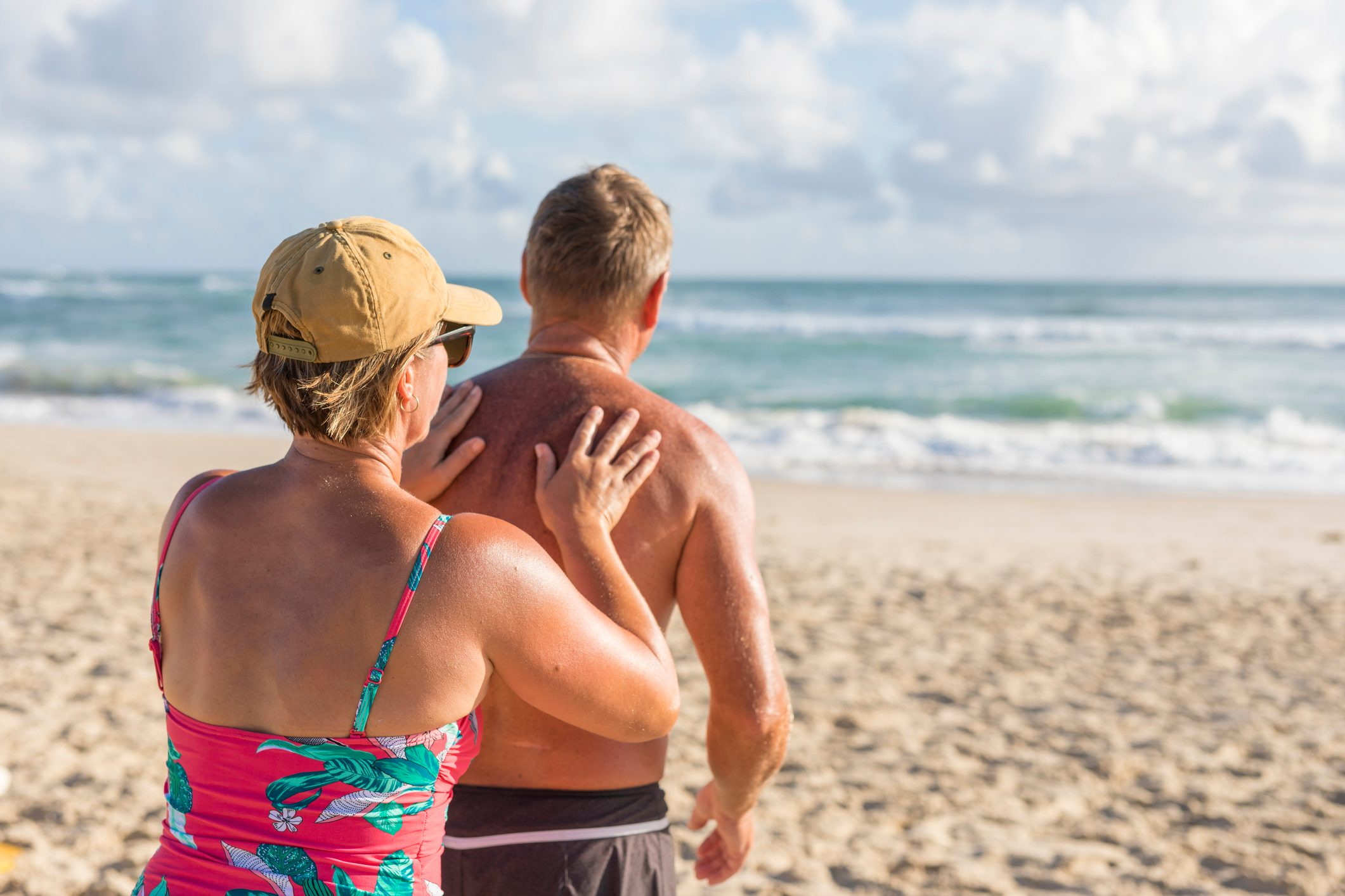 mature woman applying sunscreen to husband's back at the beach
