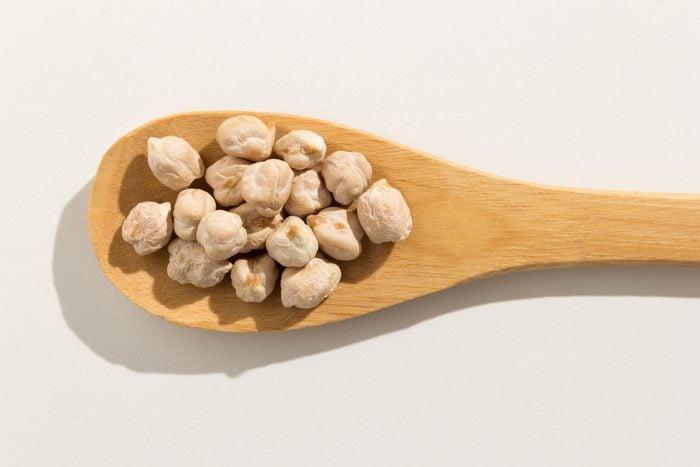 overhead shot of chickpeas in wooden spoon