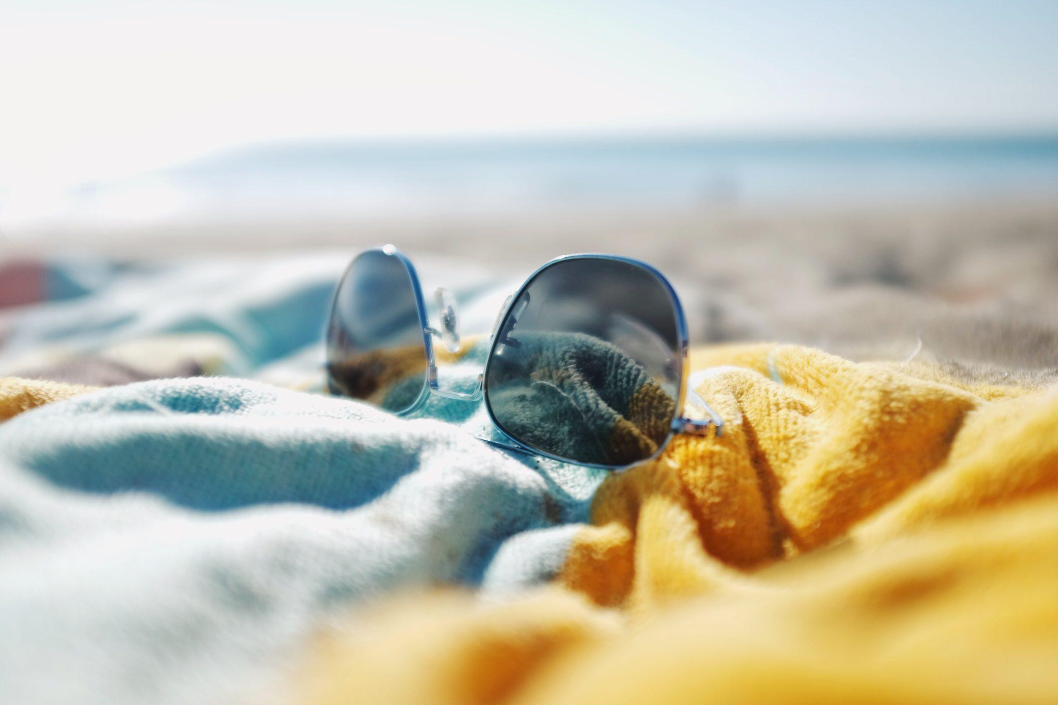 sunglasses laying on beach towel on the beach