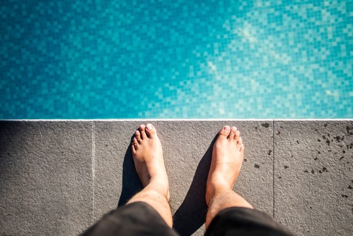 Man standing by Swimming Pool