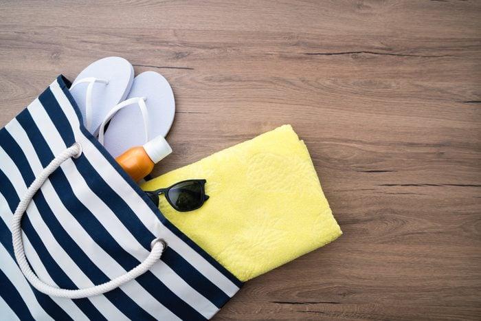 beach bag with flip flops towel and sunglasses overhead
