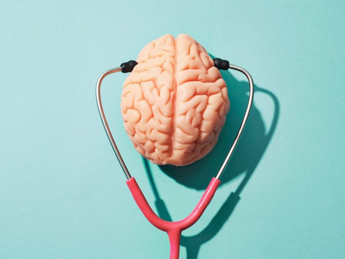 mental health conceptual image of brain model with stethoscope on blue background