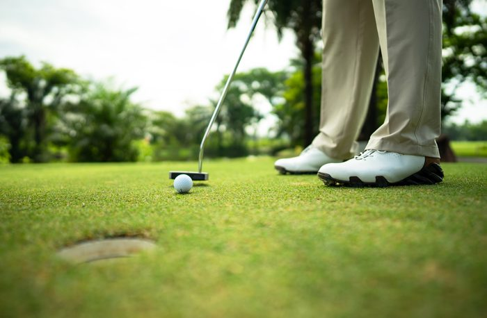 cropped shot of lower half of golfer putting on green