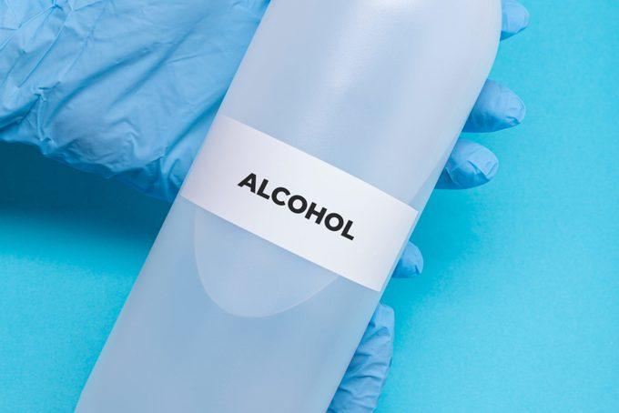 rubbing alcohol bottle on blue background