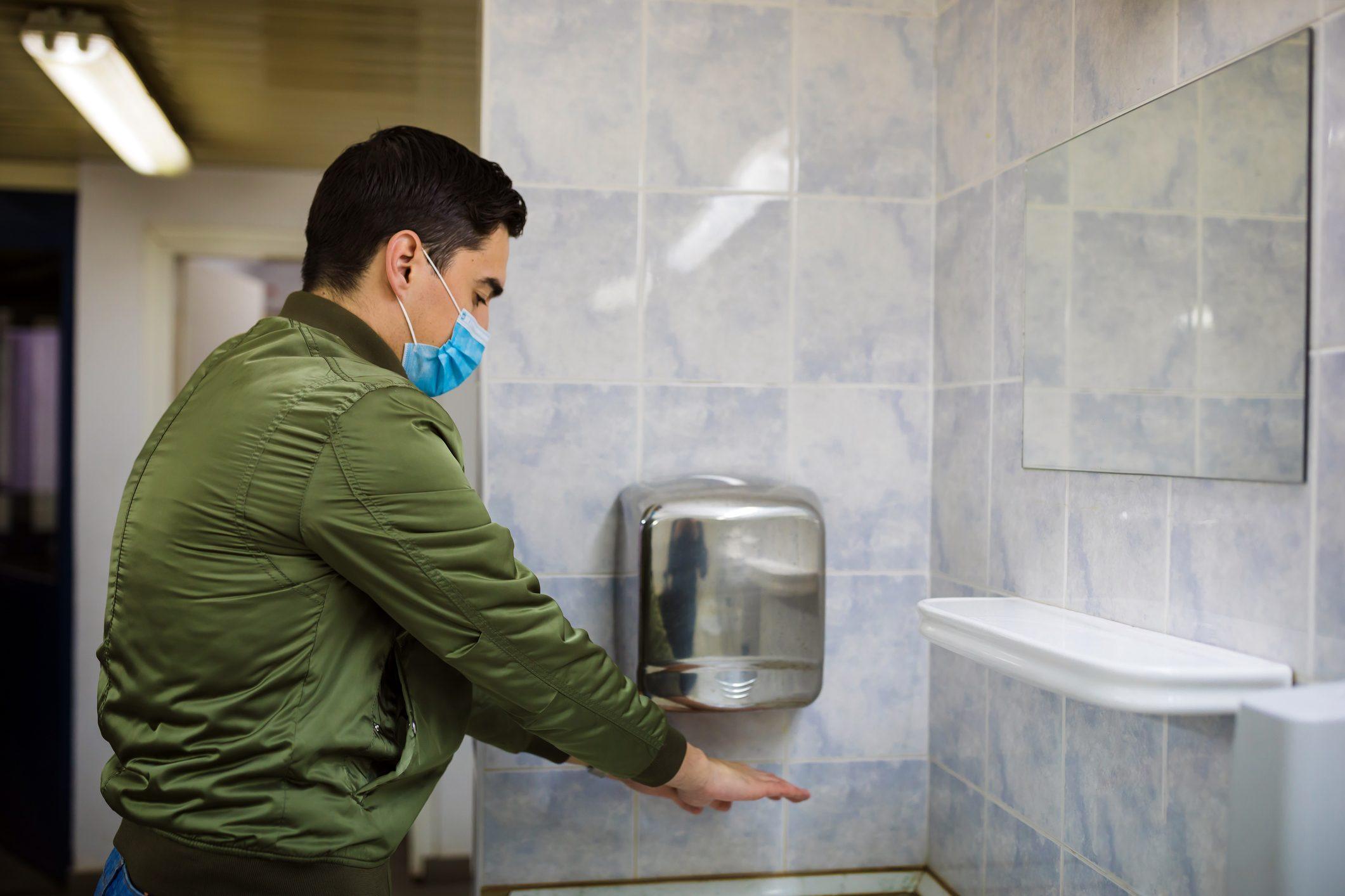 man drying hands in public restroom