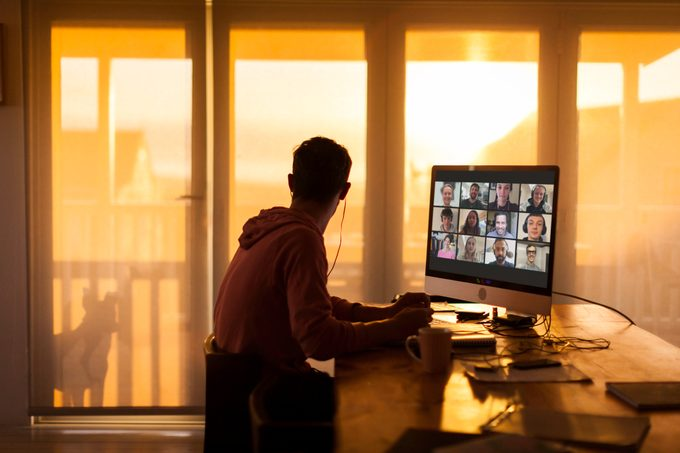 young man sitting at desk with zoom video call on computer