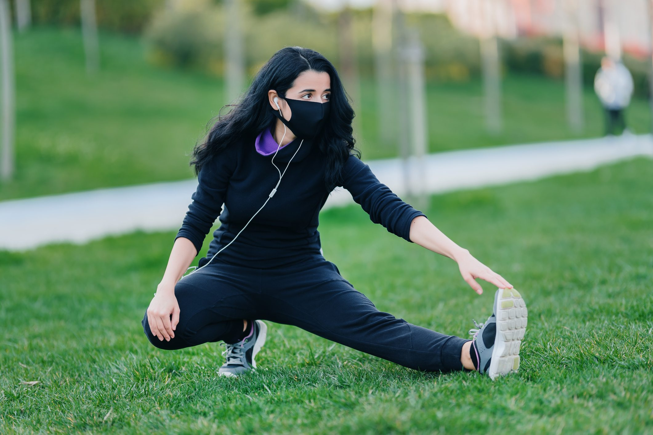 woman stretching before work out and wearing face mask protection