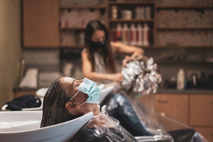 woman sitting at hair sink in salon during covid-19