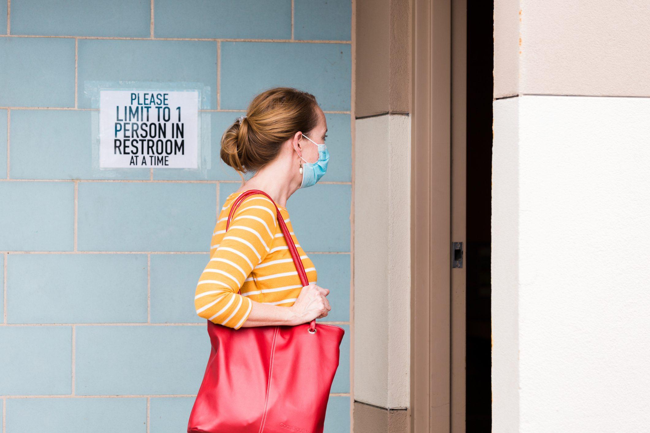 woman wearing face mask walking into public restroom