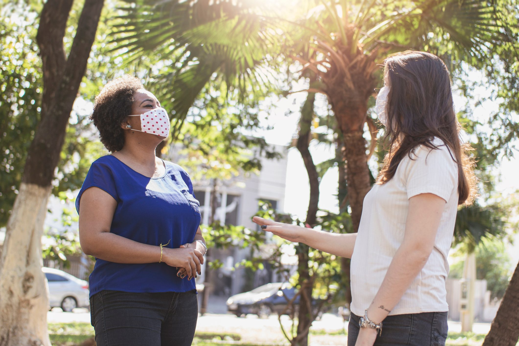 two women wearing face masks having a conversation outside