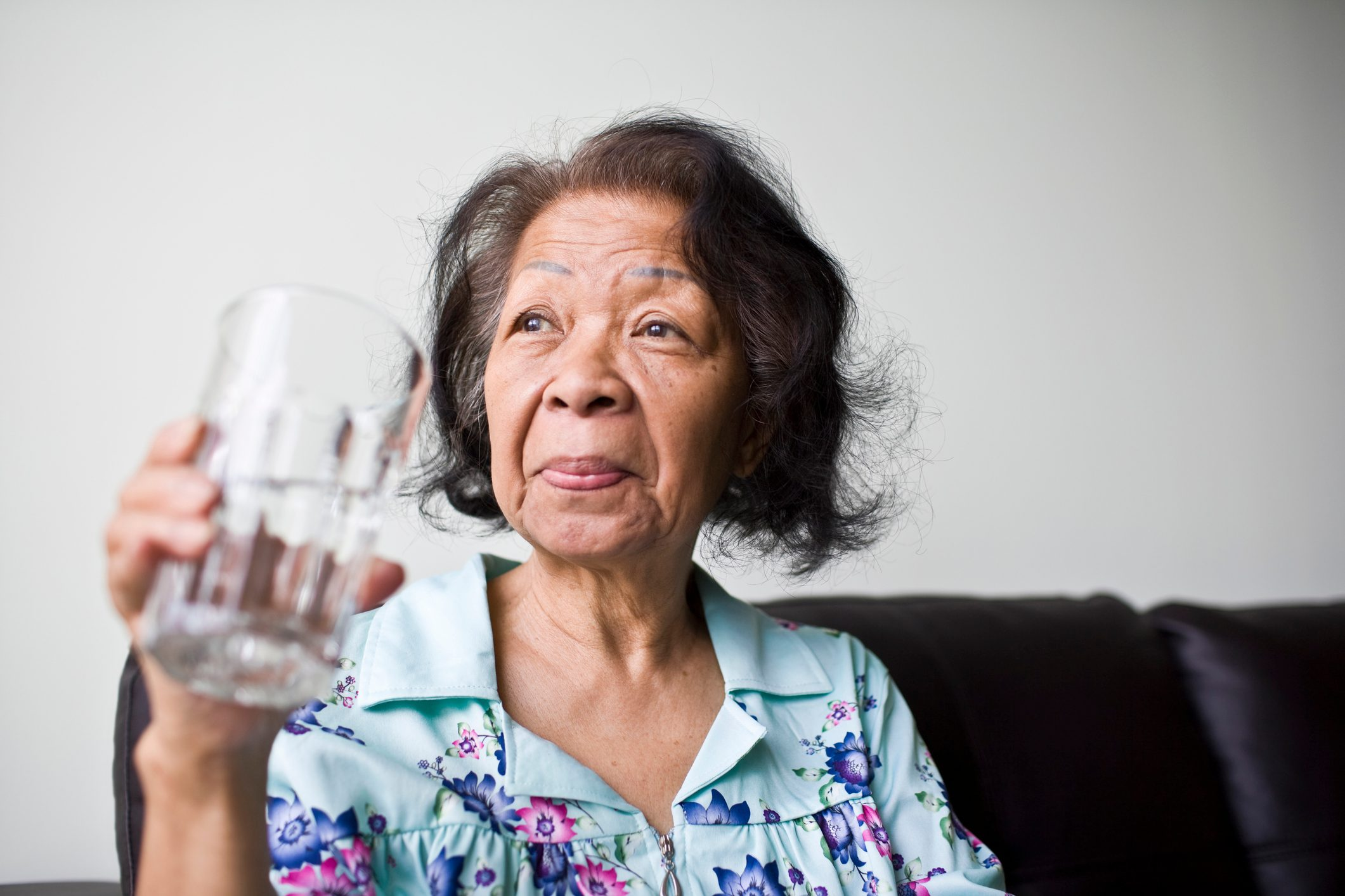 senior woman sitting on couch at home holding a glass of water
