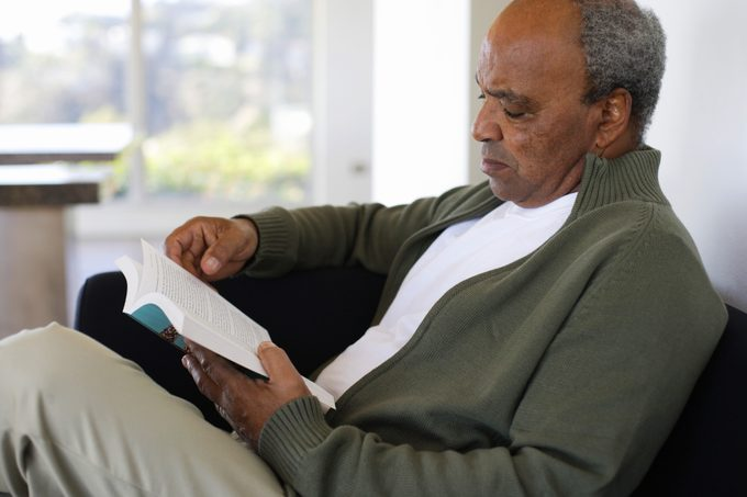 man reading a book on couch at home